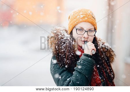 Close-up of an Ecig vaping girl holding a modern mouthpiece of an e-cigarette device in the hands of a vape. Smokes nicotine. Weather of the winter, snow. girl is warmly dressed. vaping