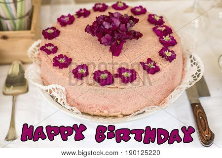 Close up cream cake with violet flowers on top silverware and colorful text happy birthday