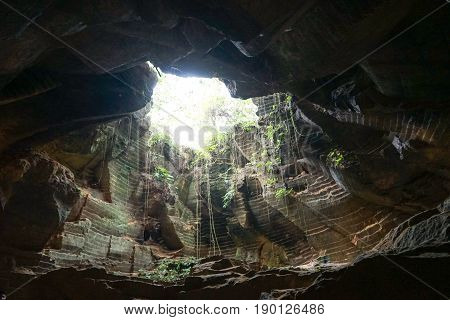 Old abandoned caves for mining of limestone with sun ray in dark enviroment in the Arosbaya, madura region in Indonesia