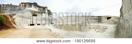 Large quarry for limestone mining mine in jaddih or jeddih hill, madura, east java, indonesia. Landscape background nature