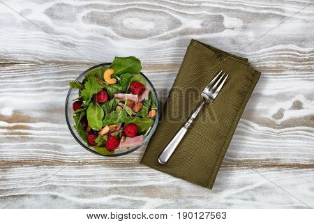 Overhead view of freshly made salad in glass bowl with fork and napkin on white wooden table