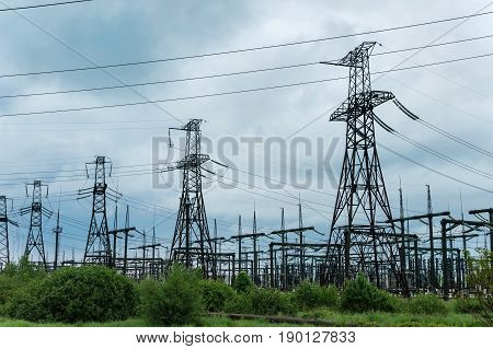 Transformer substation and high voltage tower on a background of clouds.