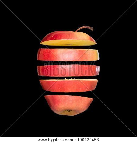 Flying apple. Sliced red apple isolated on black background. Levity fruit floating in the air