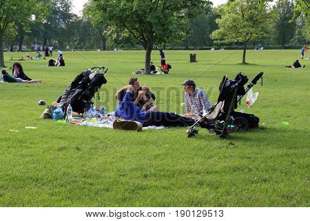 LONDON, GREAT BRITAIN - MAY 17, 2014: An unidentified group of men is resting with their children in the Regent's Park.