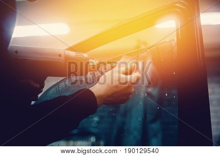 Master installs a tint film for the car glass with a hairdryer and spatula with glare of light. Concept tinting car. Toning and highlighting.