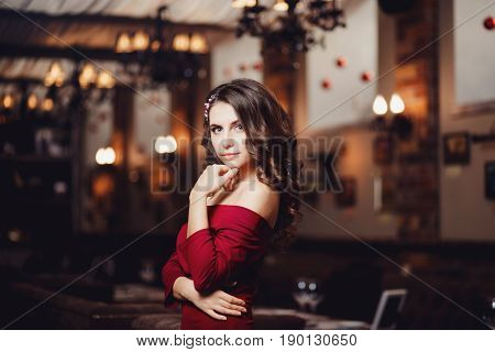 Beautiful European girl in a long cocktail evening dress of red coral with curly hair is standing in the restaurant. Concept of the make-up artist's work.