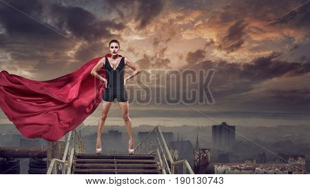 Portrait of young hero woman with super person red cape