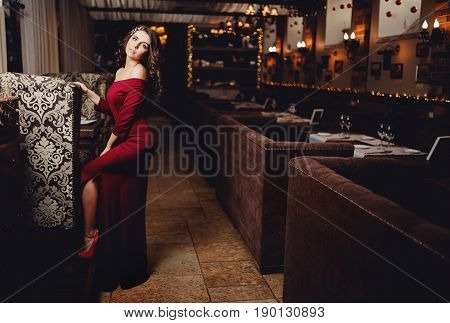 Beautiful European girl in a long cocktail evening dress of red coral with curly hair is standing in a restaurant. Concept reception is waiting for dinner and restaurant advertising.