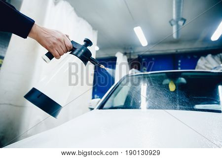 Car wash worker close-up removes stains on the car. Concept of washing a modern car with high-pressure water.