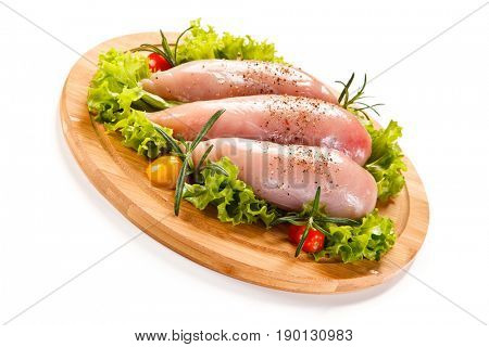 Fresh raw chicken fillet on wooden cutting board on white background