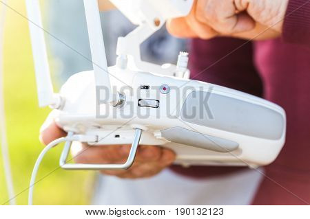 quadcopter flight outdoors, aerial imagery and tech hobby, recreation concept - closeup on white remote radio control in pilot hands, modern high-tech solution for video filming and joy flying
