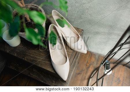 wedding beige women shoes on wooden floor. Vintage toning image