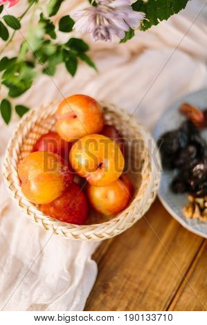 healthy life, nutrition, diet, food, country concept - close-up of red-yellow apricots lying in straw basket on snow white draping on wooden table