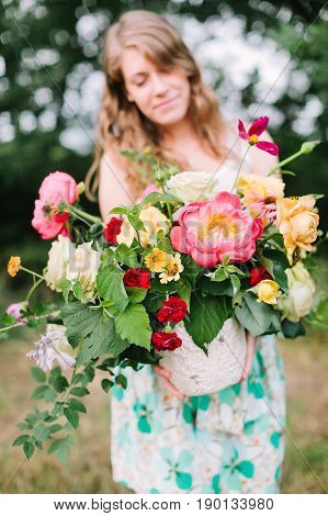 floral design, wedding, decoration, occasion concept - pretty woman in summer dress puting out grand bouquet of various flowers: big pink peonies, tender avalanches and carnations