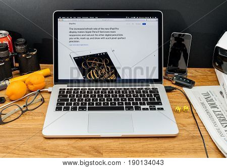 PARIS FRANCE - JUNE 6 2017: Apple Computers website on MacBook Retina in creative environment showcasing latest news from Apple at WWDC 2017 - iPad pencil on the iPad pro caligraphy