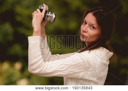 Pretty brunette woman taking a photo in a park