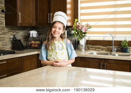 Little Chef Standing In A Kitchen And Smiling