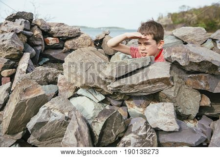 boy  playing on the rocky shore. child folded fortress of rocks and playing in it. The concept of dangerous games