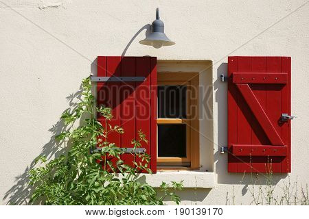Plants and nostalgic windows with red shutters and an external lamp.