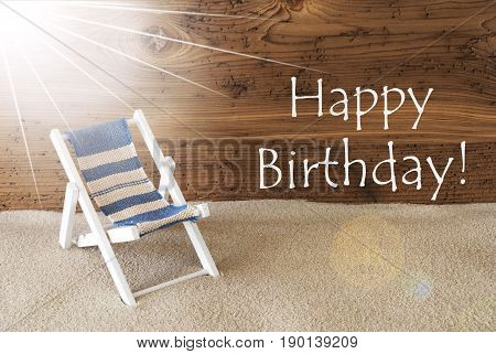 Sunny Summer Greeting Card With Sand And Aged Wooden Background. English Text Happy Birthday. Deck Chair For Holiday Or Vacation Feeling.