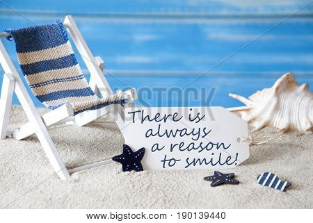 Summer Label With English Quote There Is Always A Reason To Smile . Blue Wooden Background. Card With Holiday Greetings. Beach Vacation Symbolized By Sand, Deck Chair And Shell.