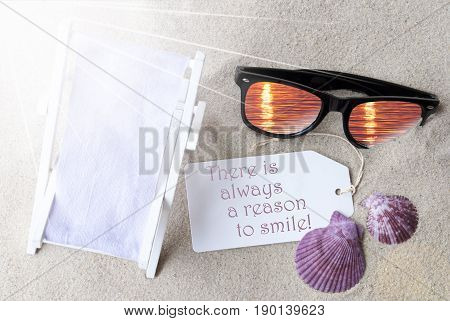Sunny Summer Label With English Quote There Is Always A Reason To Smile. Flat Lay View. Summer Decoration With Deck Chair, Seashells And Sunglasses. Greeting Crad With Sand Background
