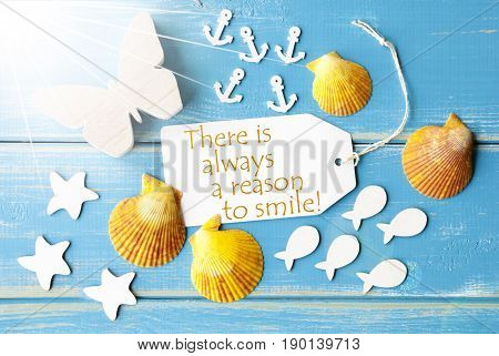 Flat Lay View Of Label With English Quote There Is Always A Reason To Smile. Sunny Summer Greeting Card. Butterfly, Shells And Fishes On Blue Wooden Background