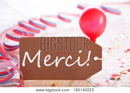 One Label With French Text Merci Means Thank You. Party Decoration Like Streamer, Confetti And Balloon. Wooden Background With Vintage, Retro Or Rustic Syle