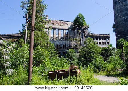 Abandoned overgrown ruins of destroyed by war Tkvarcheli (Tquarhcal) power plant, Abkhazia, Georgia