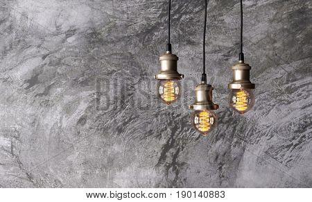 Loft pendant lamps on the background of rough cement plaster on the wall. Minimal loft interior. Edison light bulbs. 3D render.