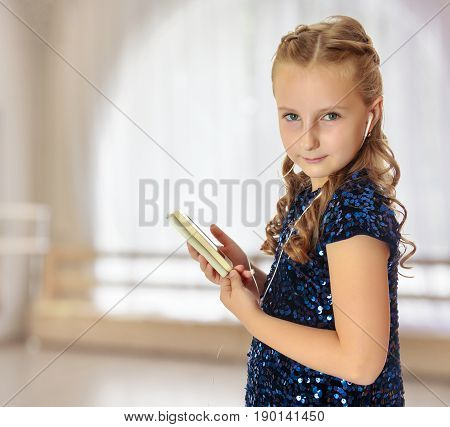 Caucasian little girl in a festive, glittering, blue dress, holding a mobile phone . She listens to music through headphones.In a room with a large semi-circular window.