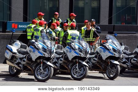 MONTREAL QC CANADA 19 05 2017: Montreal motorcycle cop in service for the little giants walking in the street of Montreal of the city it is the second largest municipal police agency in Canada