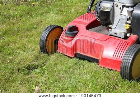 Detail of dethatcher also known as lawn scarifier - device that removes thatch from lawns; on mowed lawn; machine with gasoline engine
