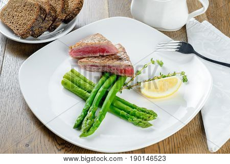 Asian grilled meat with asparagus on white pate