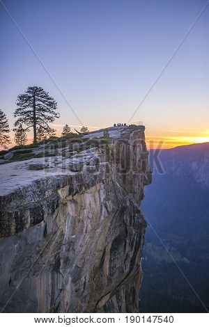 A small group of people sit at Taft Point in Yosemite at sunset.