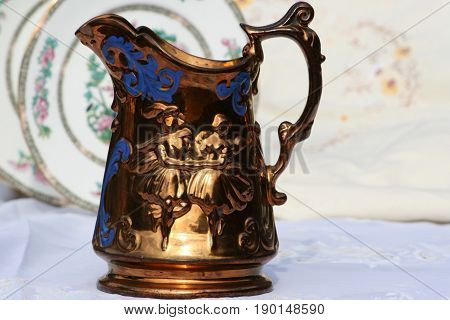 Antique copper jug with blue inlaid pattern and dancers.