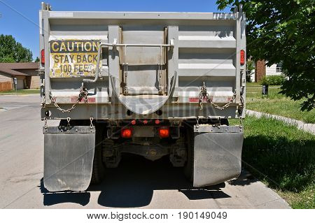 A construction parked truck parked in a residential street posts a warning sign on the rear of the box,