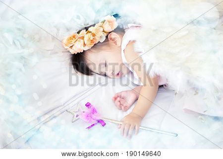 A mestizo lovely girl dressed as a fairy has a crown pastel flowers on her head sleeping and magic scepter in her hand on the couch white and white feather place surrounded and copy space