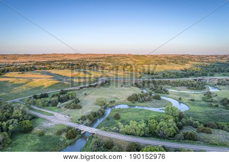 aerial view of a highway and bridge over the Dismal River in Nebraska Sandhills near Thedford, spring scenery lit by sunrise light