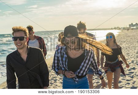 Group of young friends walking on the beach together. frienship concept. Sunset time