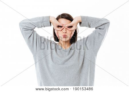 Funny girl with hands to her face like a glasses isolated over white background