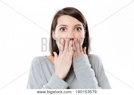 Close up portrait of a surprised astonished girl covering her mouth with hand isolated over white background