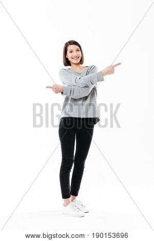 Full length portrait of an excited happy girl pointing fingers both ways isolated over white background