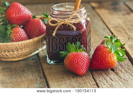 Homemade strawberry jam in bottle put on rustic wood table. Strawberry jam background with copy space for your design. Fresh strawberries in basket and homemade jam in natural tone style concept. Delicious homemade strawberry jam.
