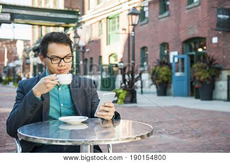 Serious young asian man in business casual attire sitting in outdoor cafe drinking cup of coffee while using mobile phone, with copy space