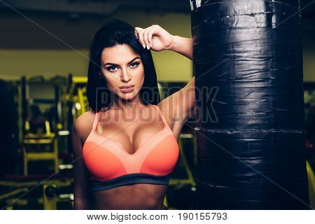 Sexy fitness model woman posing near punching bag in sport gym.