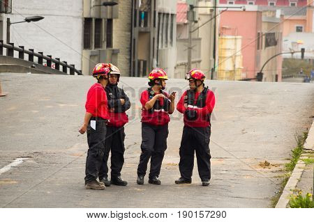Quito, Ecuador - December 09, 2016: An unidentified group of firefighter's team with equipment, talking and using their cellphones in the streets.