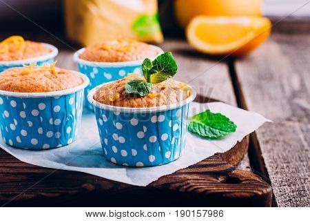 Fresh homemade orange muffin on wooden table background. Copy space. Mini cake with corn flour. Healthy bakery food.