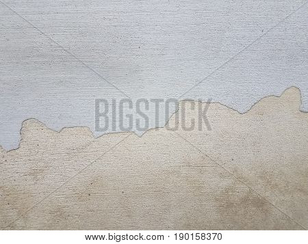 an irregularly shaped line dividing white and grey cement