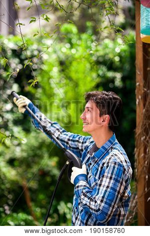Handsome smiling young man wearing square pattern blue holding high pressure water gun, on a garden background.